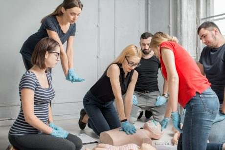 first aid heart compressions with dummies during the training indoors